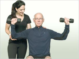 older person working out with weights and trainer