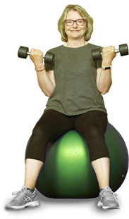 survivor of cancer on exercise ball with weights